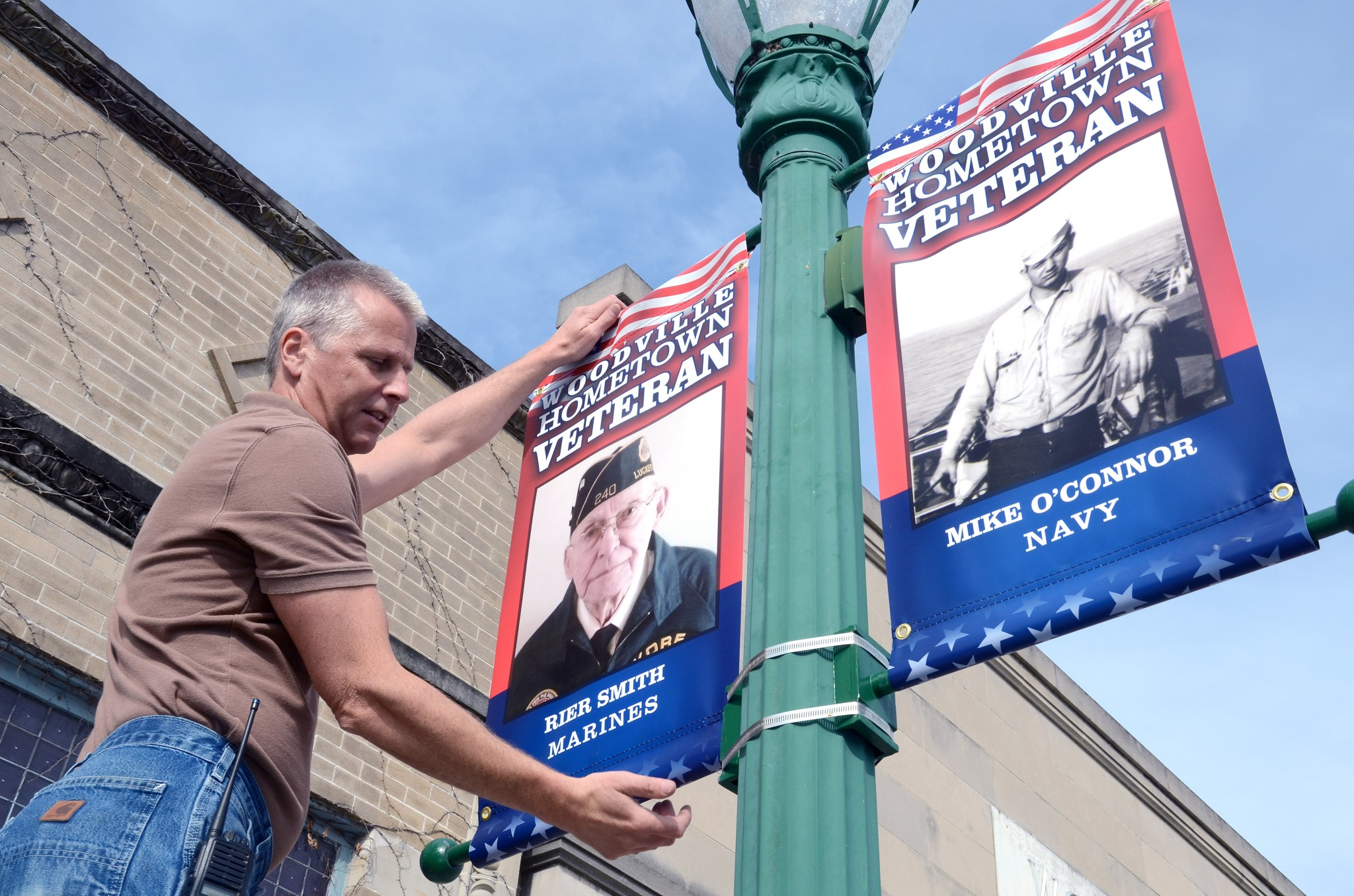 Keith Kruse, Village of Woodville, in front of the Woodville Public Library, with two of the 102 banners honoring veterans. (Press photo by ken Grosjean)